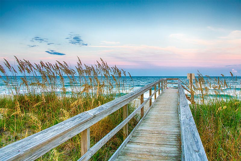 A wooden path leads to a beach in Wilmington North Carolina
