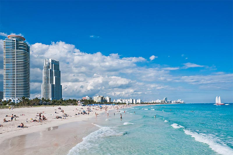 Condominium buildings on the left, rising above the beach in South Beach Miami Florida