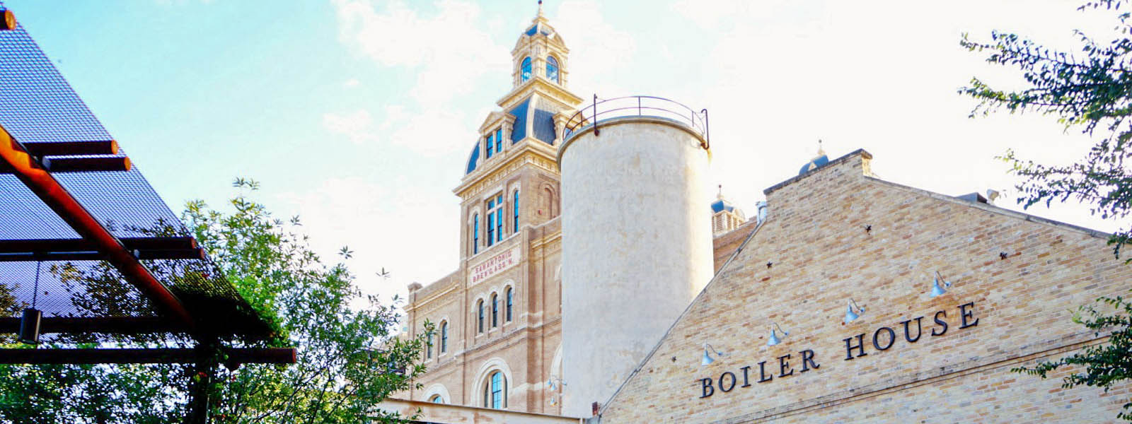 A scene in Tobin Hill San Antonio of a brewery with a large, historic building behind it against a blue sky