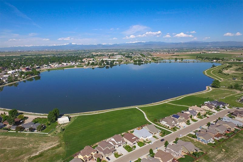 A large lake sits between rows of houses with mountains seen in the very far distance in Denver